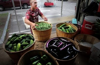 Kevin Bragg of Kimball Fruit Farm unloads produce at the Brookline Farmers Market in Coolidge Corner